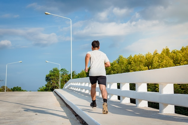 The man with runner on the street at bridge be running for exercise