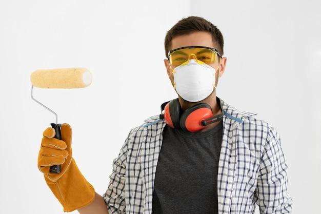 Uomo con verniciatura di attrezzature di protezione di sicurezza