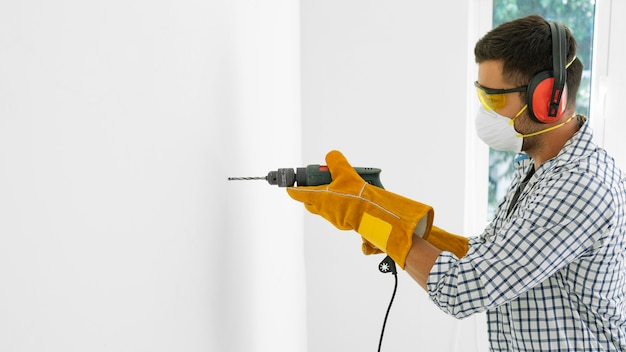 Man with safety protection equipment with drill