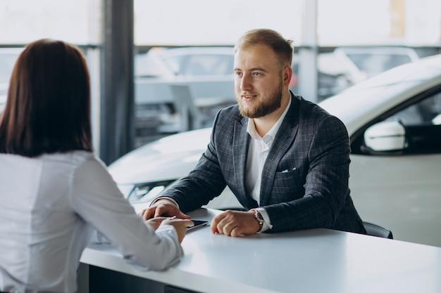 Uomo con donna di vendita in autosalone