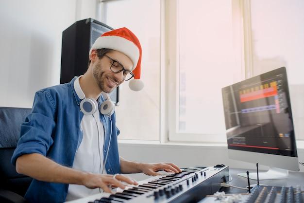 Человек в шляпе санта играет на пианино в студии