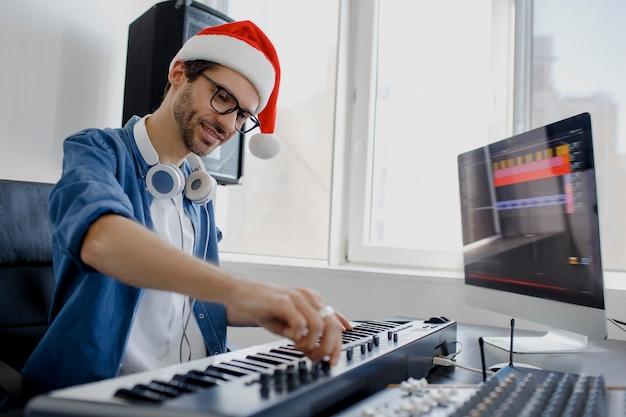 스튜디오에서 피아노를 연주하는 산타 모자를 가진 남자