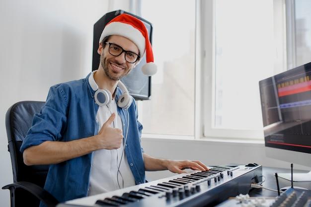 피아노 연주 산타 모자를 가진 남자