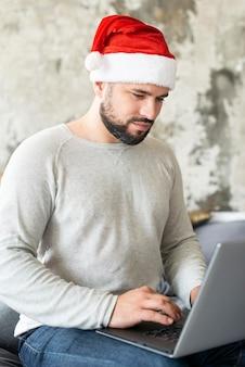 Человек в шляпе санта-клауса смотрит на свой ноутбук на рождество