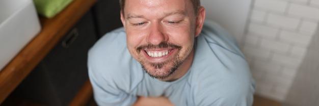 만족스러운 미소를 가진 남자가 변기에 앉아 있다