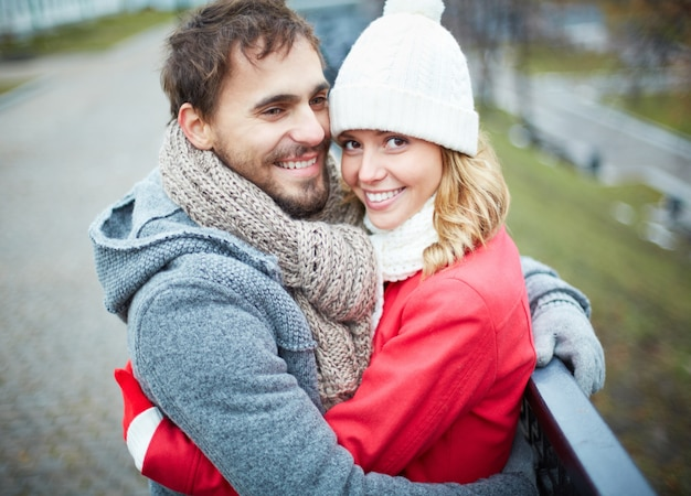 Man with scarf hugging his girlfriend outdoors