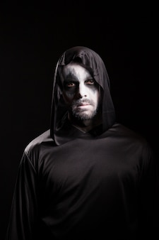 Man with scary make up for halloween wearing a hood isolated over black background.