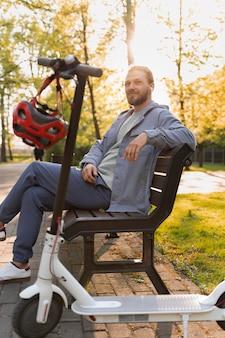 ベンチに座っているスクーターを持つ男