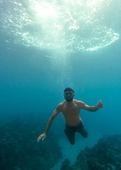 바다에서 수영하는 스쿠버 장비를 가진 남자