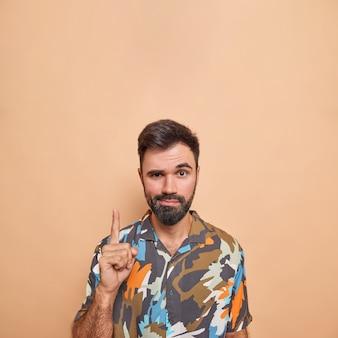 自信に満ちた表情の男性は、上向きのショーを示していますプロモーションバナーは、2階に行くことをお勧めしますベージュのカラフルなシャツのポーズを着ています