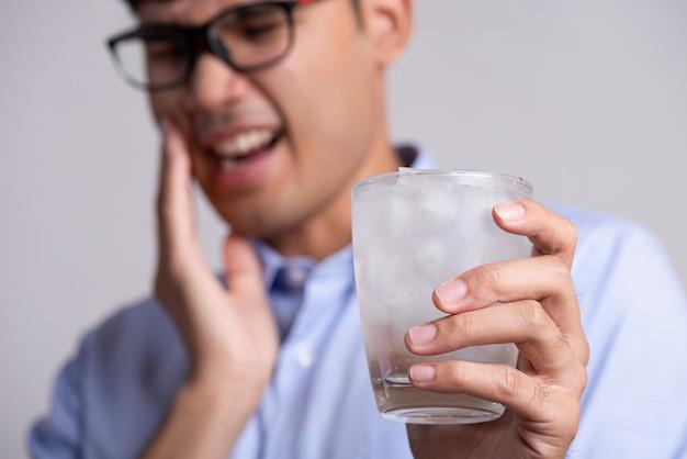 敏感な歯と冷たい水のガラスを持っている手を持つ男。医療コンセプト。