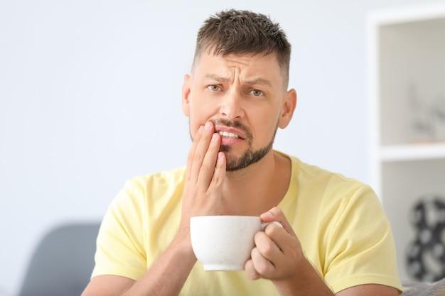 Человек с чувствительными зубами и горячим кофе дома