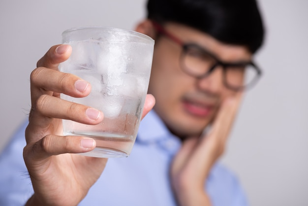 Man with sensitive teeth and holding glass of cold water with ice