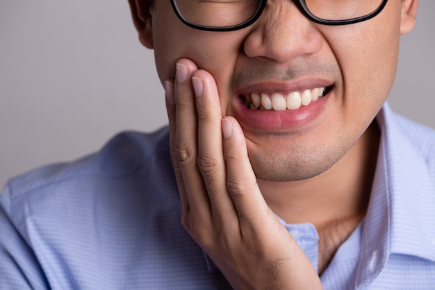 Man with sensitive teeth or toothache. healthcare concept.