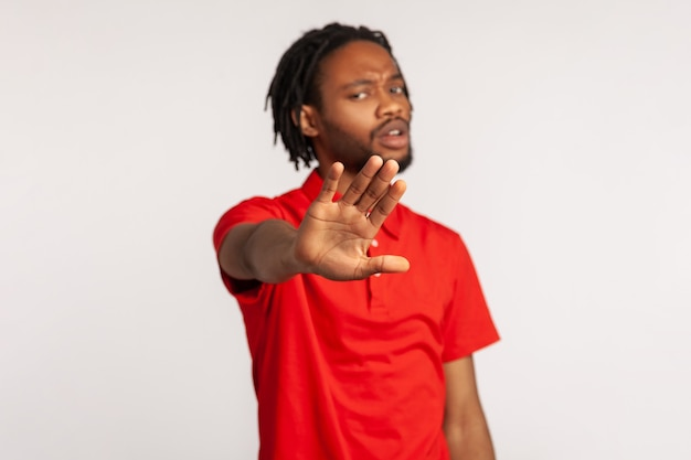 Man with serious face showing stop gesture with his palm, being against bullying and violence.