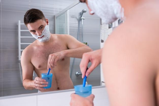 뺨에 면도 거품이 있는 남자는 집의 현대적인 타일 욕실에서 거울 앞에 서 있는 물로 컵에 면도기를 씻습니다