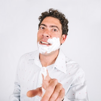 Man with shaving foam pointing at camera