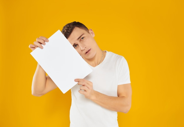 Man with sheet of paper advertising copy space presentation yellow background. high quality photo