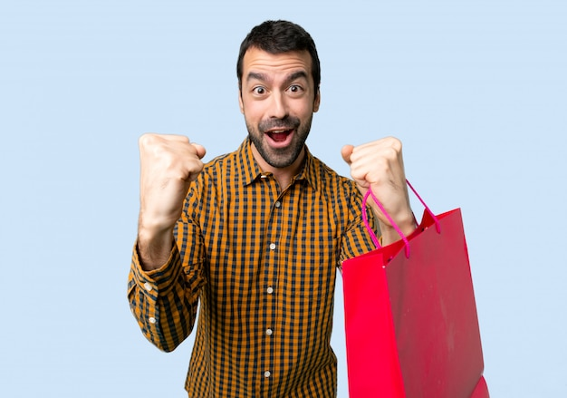 Man with shopping bags celebrating a victory in winner position on isolated blue background