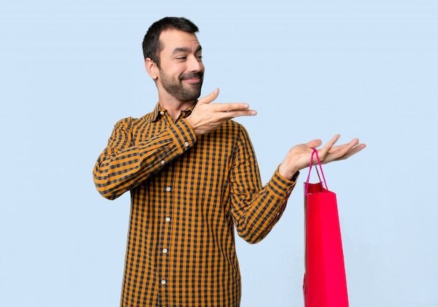 Man with shopping bags extending hands to the side for inviting to come on isolated blue background