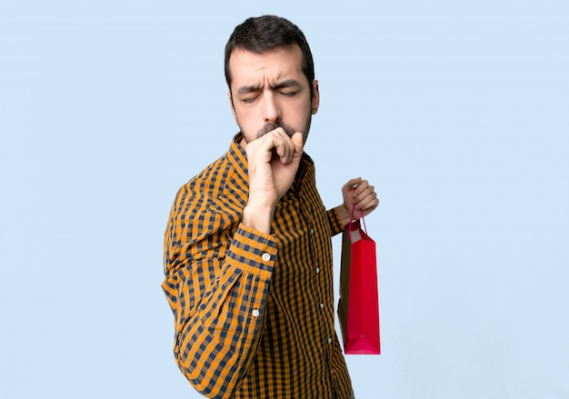 Man with shopping bags is suffering with cough and feeling bad on isolated blue background