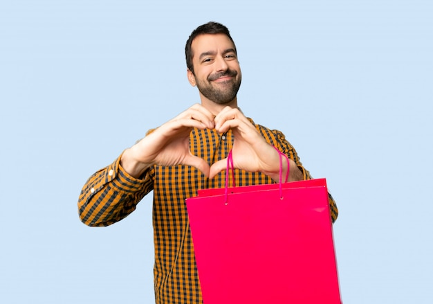 Man with shopping bags making heart symbol by hands on isolated blue background
