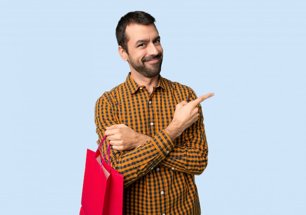 Man with shopping bags pointing to the side to present a product on isolated blue background
