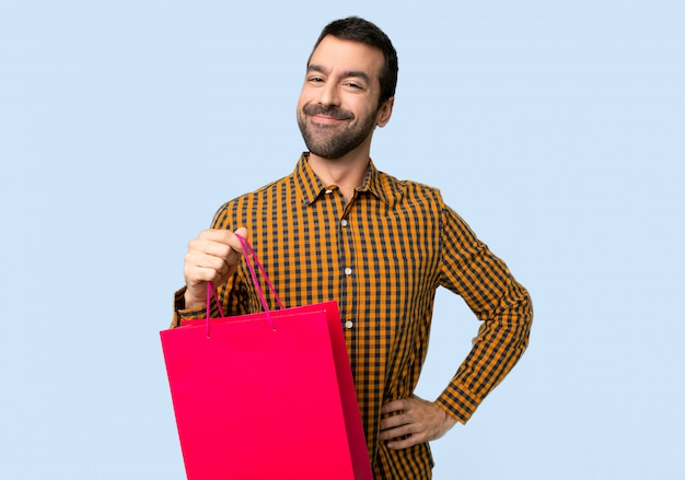 Man with shopping bags posing with arms at hip and smiling on isolated blue background