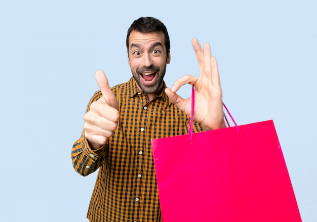 Man with shopping bags showing ok sign with and giving a thumb up gesture on isolated blue background