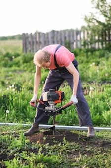 地面を掘るシャベルを持つ男
