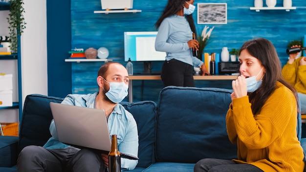 コロナウイルスに対して社会的な距離を保ちながら、新しい通常のパーティーで女性と話しているラップトップを持ってソファに座っている男性