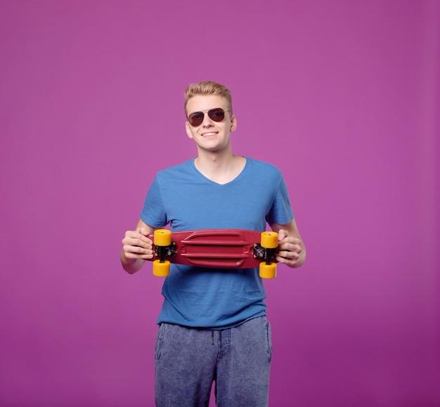 紫色の背景にスケートボードを手に、ペニー小さなボードを持つ男
