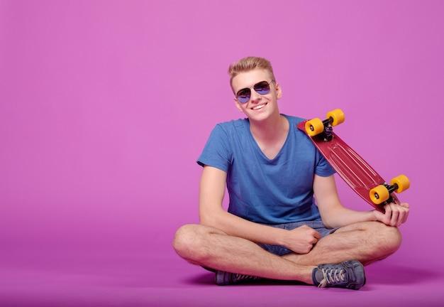 Человек с скейтбордом в руке на фиолетовом фоне