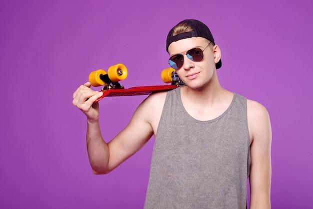 Человек с скейтбордом в руке на фиолетовом