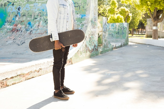Man with skateboard in urban environment