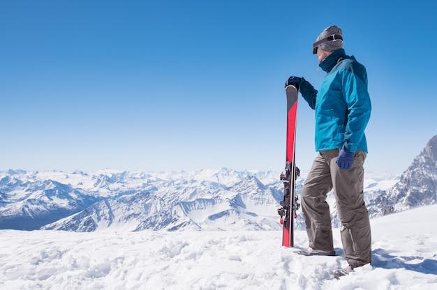 山の上にスキーを持つ男
