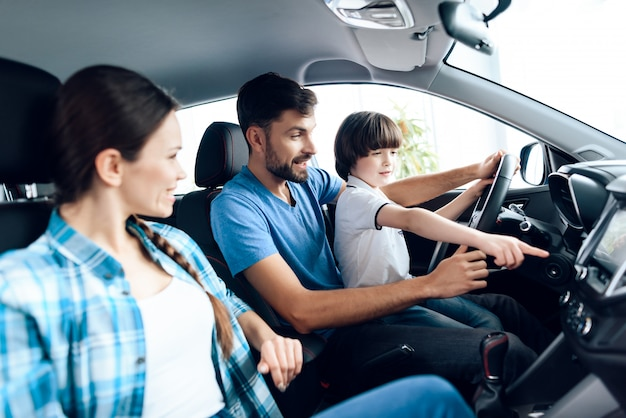 A man with a small son is sitting at the wheel of the car.