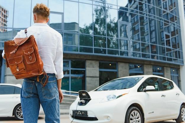 Человек со смартфоном после завершения зарядки аккумулятора. мужчина возле электромобиля