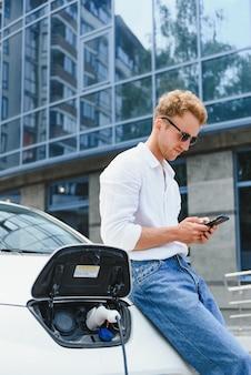 배터리 충전을 마친 후 스마트폰을 든 남자. 전기 자동차 근처 남성