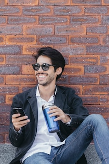 Man with smartphone and cup near wall