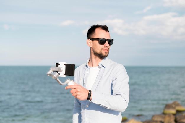海辺でスマートフォンを持つ男