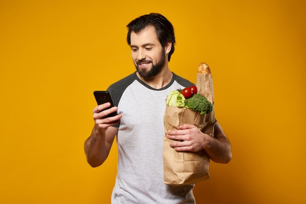 Man with smartphone holds paper bag with fresh products.