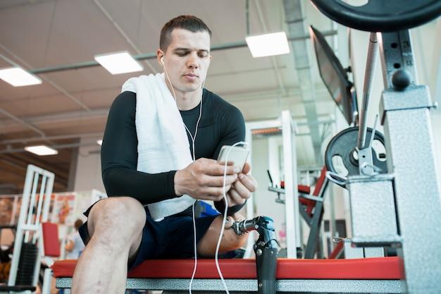 Человек с смартфон в тренажерном зале