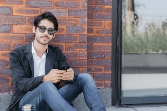 Man with smartphone looking at camera