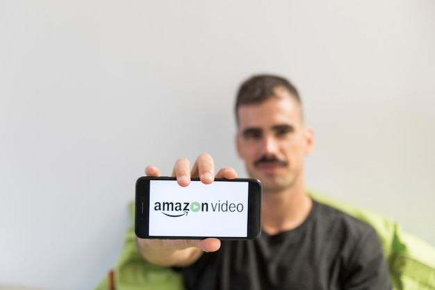 Man with smartphone showing amazon prime video app