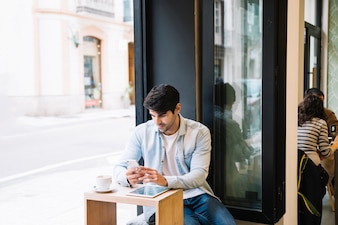 Man with smartphone sitting in cafe