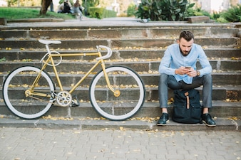 Man with smartphone sitting near bicycle