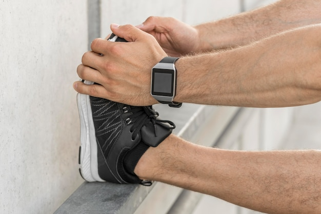 Man with smartwatch stretching outside
