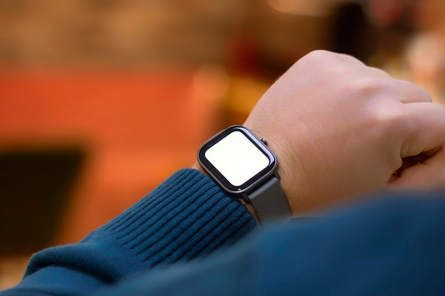A man with a smartwatch and a white screen mockup on his hand. a man uses a fitness tracker on the background of a shopping mall.