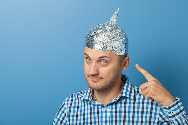 Man with smiles and shows a finger at a hat with aluminum foil. protects from reading think.
